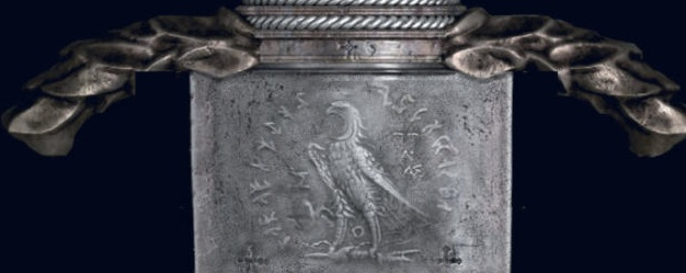 Figure 9: the hilt of WW's sword in BvS. An eagle representing Zeus clutches a thunderbolt in its talons with still-mysterious writing on either side. Photo credit: scan from Batman v Superman: Tech Manual.