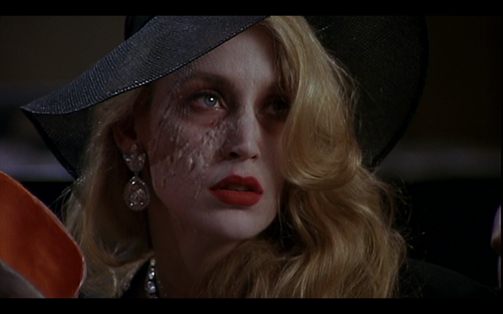 Figure 1: After killing the patrons of the Fulgelheim Museum, the Joker reveals his girlfriend Alicia's scarred face to Vicky Vale in Batman. Photo credit: Warner Brothers (DVD).