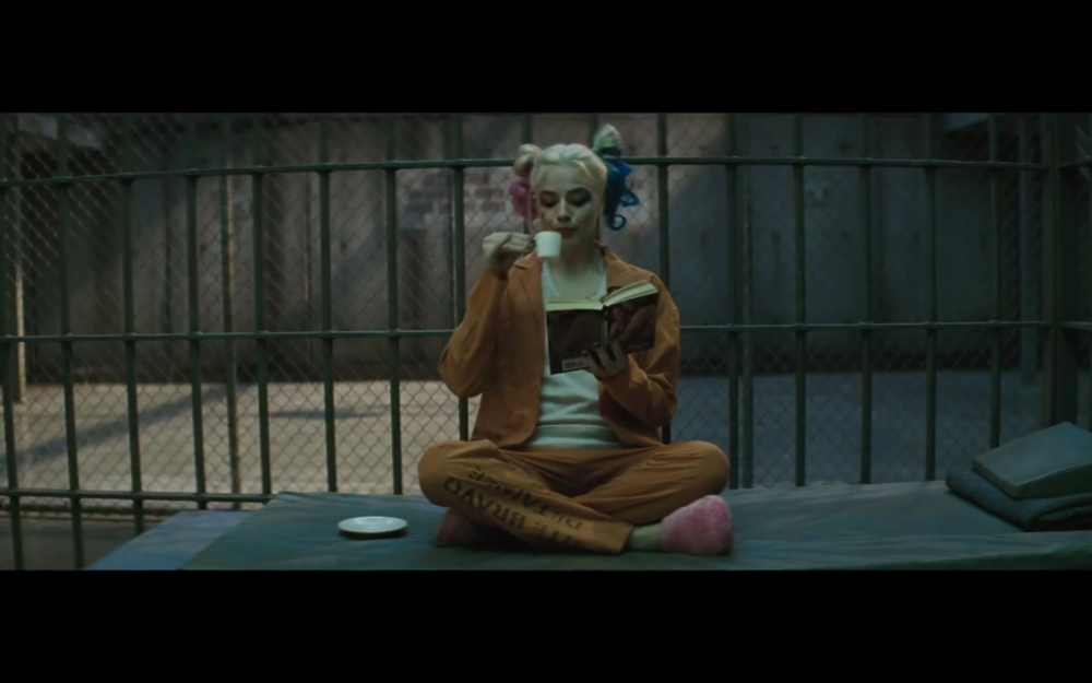Figure 6: Harley reads a Harlequin Romance in her cell in  Suicide Squad  trailer #2. Photo credit: Atlas Entertainment/DC Comics (screen capture).