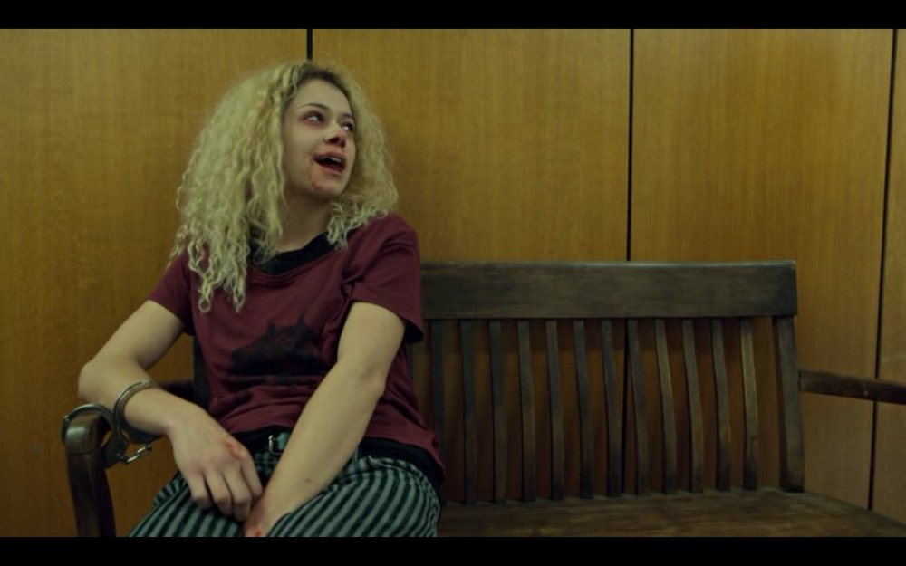 "Figure 2: In ""Governed As It Were By Chance"" (2.6), Helena sits on a bench in a police station, her mouth bloodstained from her barroom brawl. Photo credit: screen capture (Temple Street Productions),"