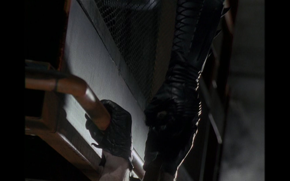 Figure 4: When Napier tumbles over the catwalk, Batman tries to save him, but the criminal's leather gloves slip, first off the railing and then from the vigilante's hand, and he falls into a vat of chemicals in Burton's  Batman .
