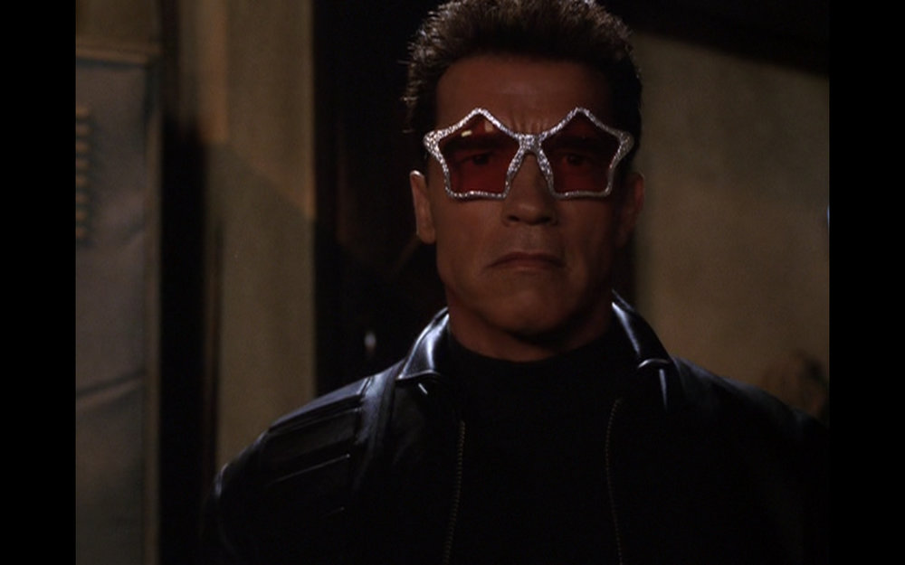 Figure 1: In  T3  Schwarzenegger's T-850 model first dons star-shaped sunglasses worn by the source of its clothes, a male stripper, but almost instantly crushes them underfoot. In the next shot it steals a truck and puts on the sunglasses it finds inside, which are similar to the pair the T-800 wore in  T1  and  T2 . The film simultaneously alludes to and also asserts its improvements on Cameron's previous entries in a playful way.