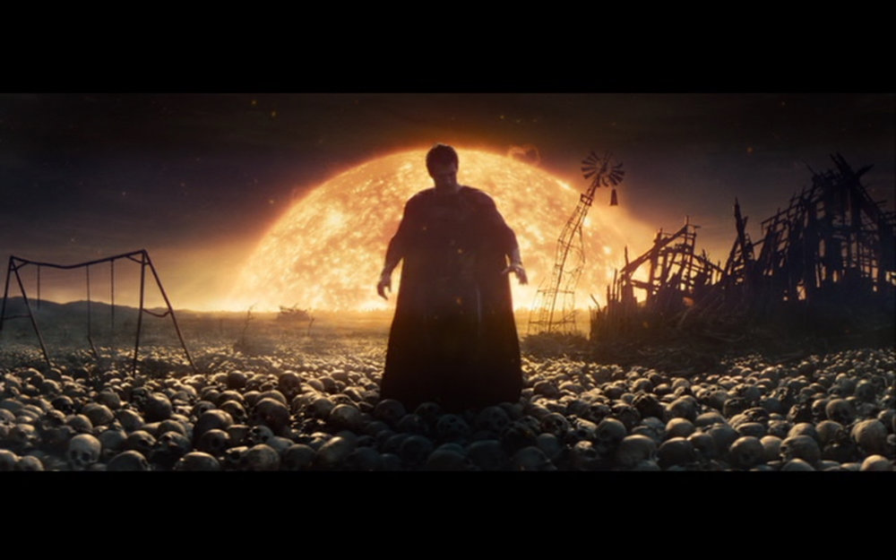 Figure 3: Aboard Zod's ship, Kal has a vision of Earth's future at the hands of Zod: a fiery apocalypse, with human skulls littering the ground. The twisted swing set in the background recalls the hellscape of the post-Judgment Day future of  Terminator 2  (Cameron 1991).
