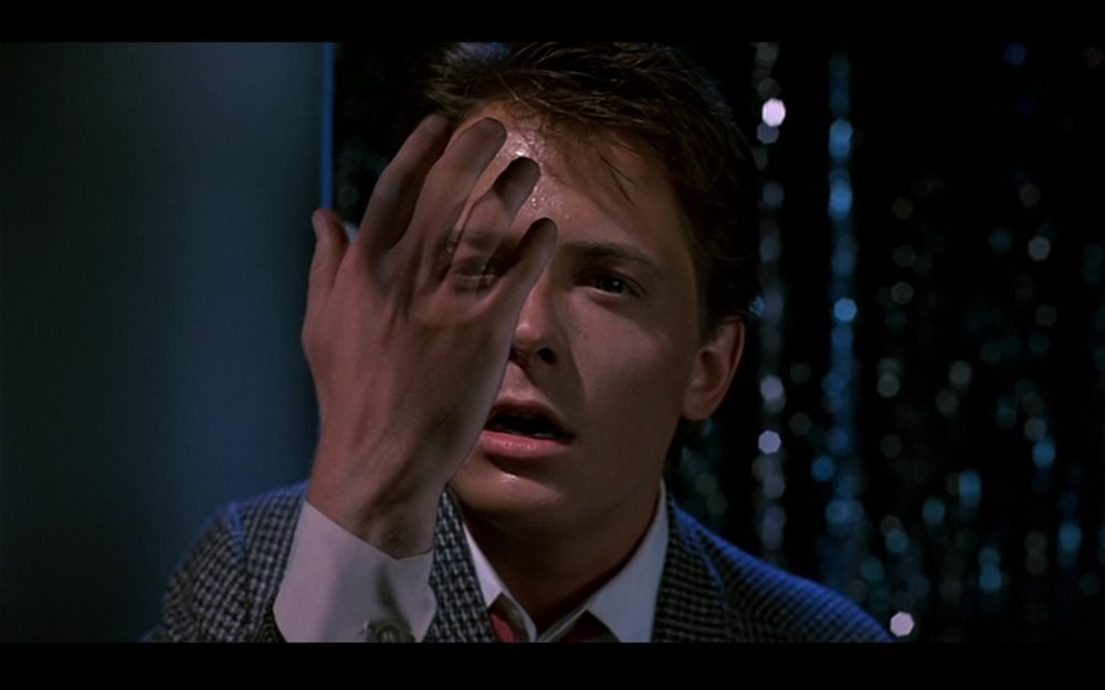 Figure 1: We see Marty's fingers become translucent as he begins to phase out of existence as a result of his mother and father growing further apart in the past in  Back to the Future  (Zemeckis 1985).