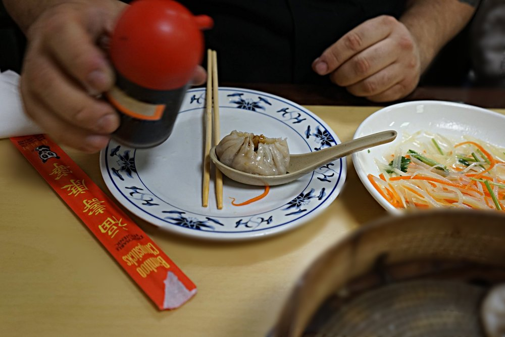 Proper way to eat a soup dumpling: Carefully nibble the top off, then pour 1 maybe 2 drops of black vinegar inside....you're welcome.
