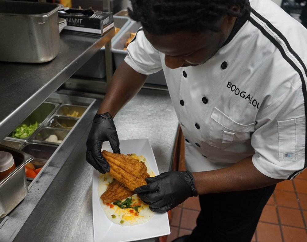 Executive Chef Robert Joiner plating up Catfish and Grits
