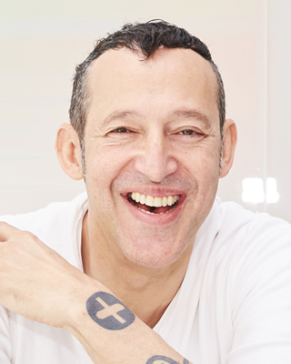 Karim Rashid, Founding Partner      Chief Design Director     Karim Rashid is one of the most prolific designers of his generation. Over 3000 designs in production, over 300 awards and working in over 40 countries attest to Karim's legend of design.    His award winning designs include luxury goods for Christofle, Veuve Clicquot, and Alessi, democratic products for Umbra, Bobble, and 3M, furniture for Bonaldo and Vondom, lighting for Artemide and Fabbian, high tech products for Asus and Samsung, surface design for Marburg and Abet Laminati, brand identity for Citibank and Sony Ericsson and packaging for Method, Paris Baguette, Kenzo and Hugo Boss.  Karim's touch expands beyond product to interiors such as the Morimoto restaurant, Philadelphia; Semiramis hotel, Athens; nhow hotel, Berlin; Universita Metro Station, Naples as well as exhibition design for Deutsche Bank and Audi.  Karim's work is featured in 20 permanent collections and he exhibits art in galleries world wide. Karim is a perennial winner of the Red Dot award, Chicago Athenaeum Good Design award, I. D. Magazine Annual Design Review, IDSA Industrial Design Excellence award.     Karim is a frequent guest lecturer at universities and conferences globally disseminating the importance of design in everyday life. He holds Honorary Doctorates from the OCAD, Toronto and Corcoran College of Art & Design, Washington. Karim has been featured in magazines and books including Time, Vogue, Esquire, GQ, Wallpaper, and countless more.  Karim's latest monograph, XX (Design Media Publishing, 2015), features 400 pages of work selected from the last 20 years. Other books include From The Beginning, an oral history of Karim's life and inspiration (Forma, 2014); Sketch, featuring 300 hand drawings (Frame Publishing, 2011); KarimSpace, featuring 36 of Karim's interior designs (Rizzoli, 2009); Design Your Self, Karim's guide to living (Harper Collins, 2006); Digipop, a digital exploration of computer graphics (Taschen, 2005); Compact Design Portfolio (Chronicle Books 2004); as well as two monographs, titled Evolution (Universe, 2004) and I Want to Change the World (Rizzoli, 2001).  In his spare time Karim's pluralism flirts with art, fashion, and music and is determined to creatively touch every aspect of our physical and virtual landscape.
