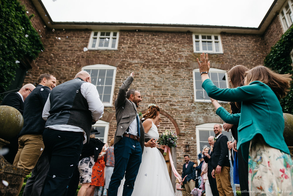 Throwing confetti and cheering for the bride and groom as the leave the main entrance of Dewsall Court,