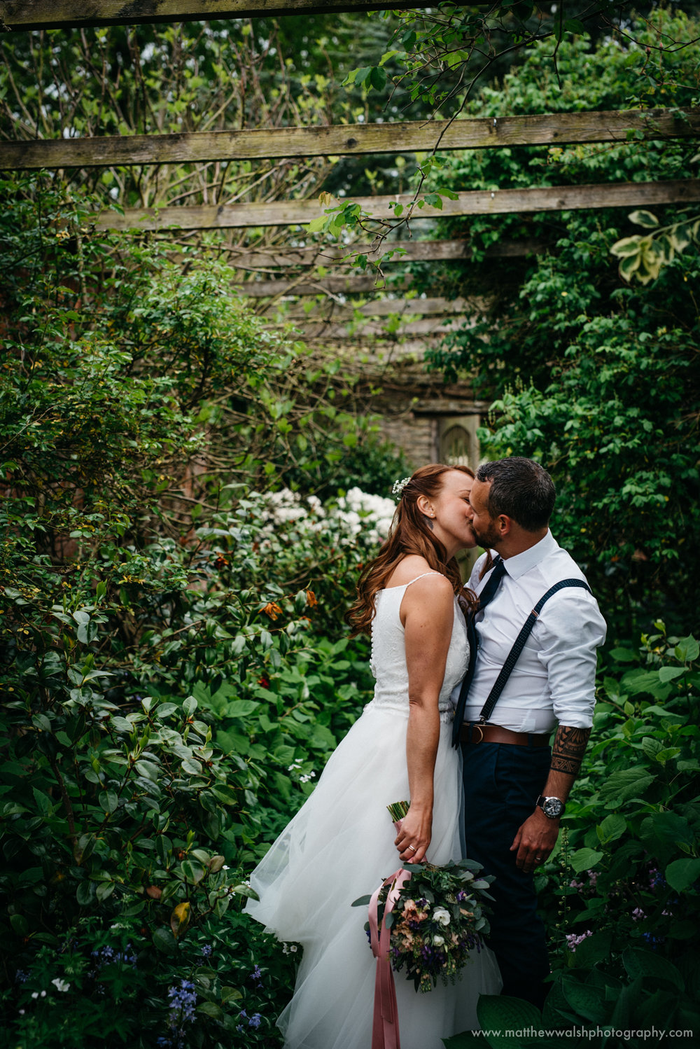A very intimate moment for the bride and groom as they kiss in the gardens