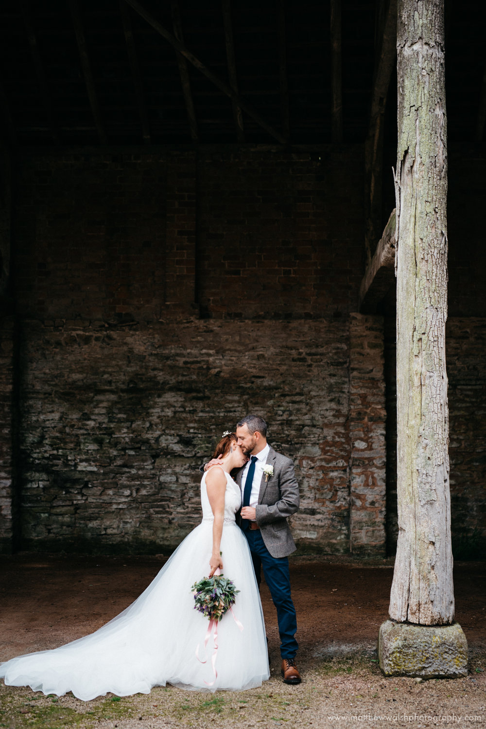 The happy couple have a hug under the shelter of a barn at the venue
