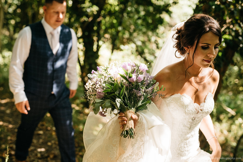 A stunning artistic photograph as the bride and groom walk through the amazing forest backdrop
