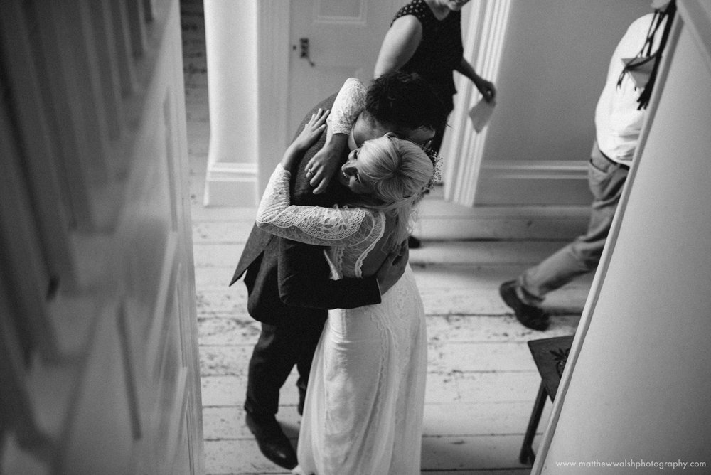 a very happy bride embraces her brother