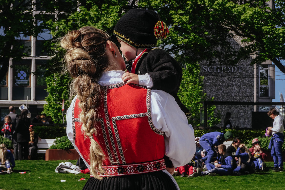 "People traditionally wear their folk costume (called ""bunad"") on May 17th and every region in Norway has its own particular kind. If you don't have a bunad, you can just wear your nicest dress/suit and get a ribbon in the Norway colours to pin to the left side of your chest to show your love for the country!"