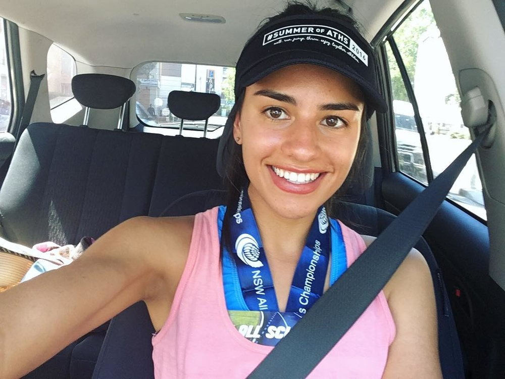 Imogen Russell takes a selfie, sat in the front seat of a car, smiling with a medal around her neck