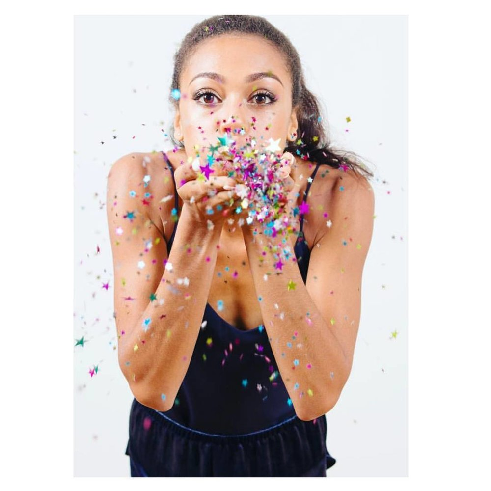 Adelle Tracey blows glitter out of her hands towards the camera