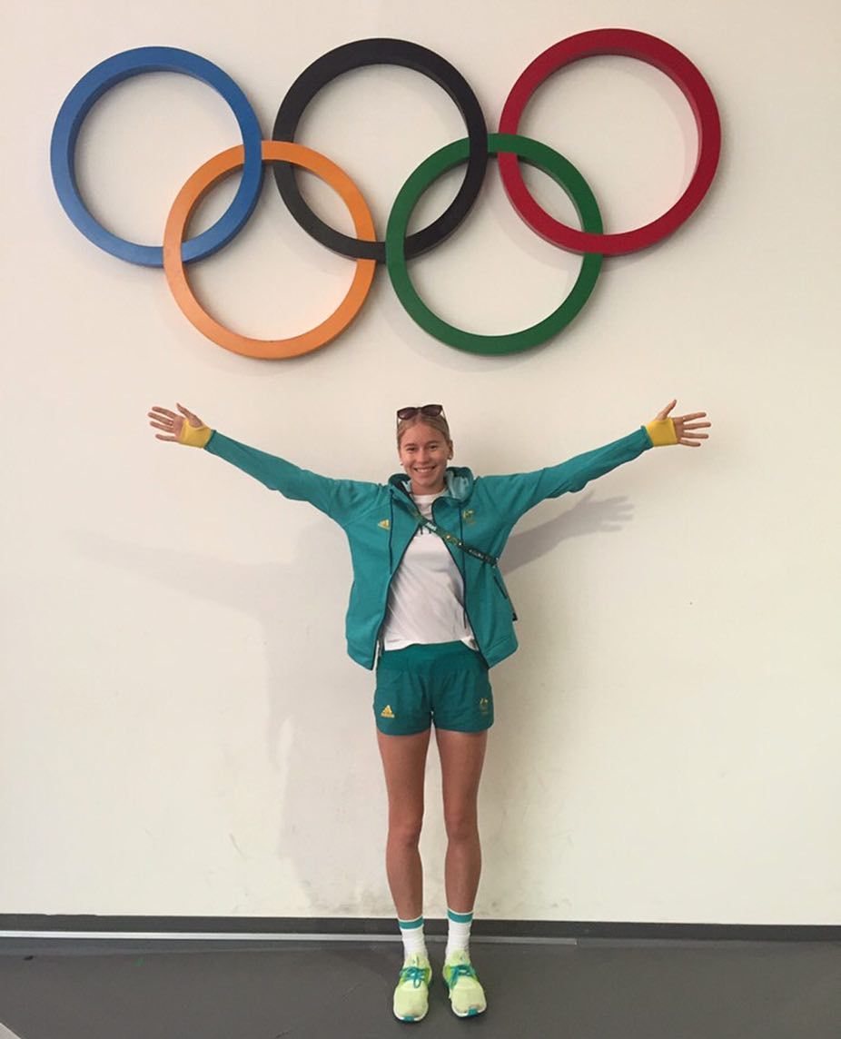 Eleanor Patterson, standing with arms out stretched in front of the Olympic rings logo at Rio 2016