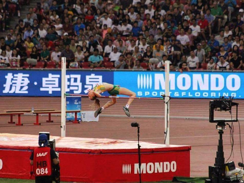 Eleanor Patterson mid-high jump in a large stadium, with the crowd looking on in the distance