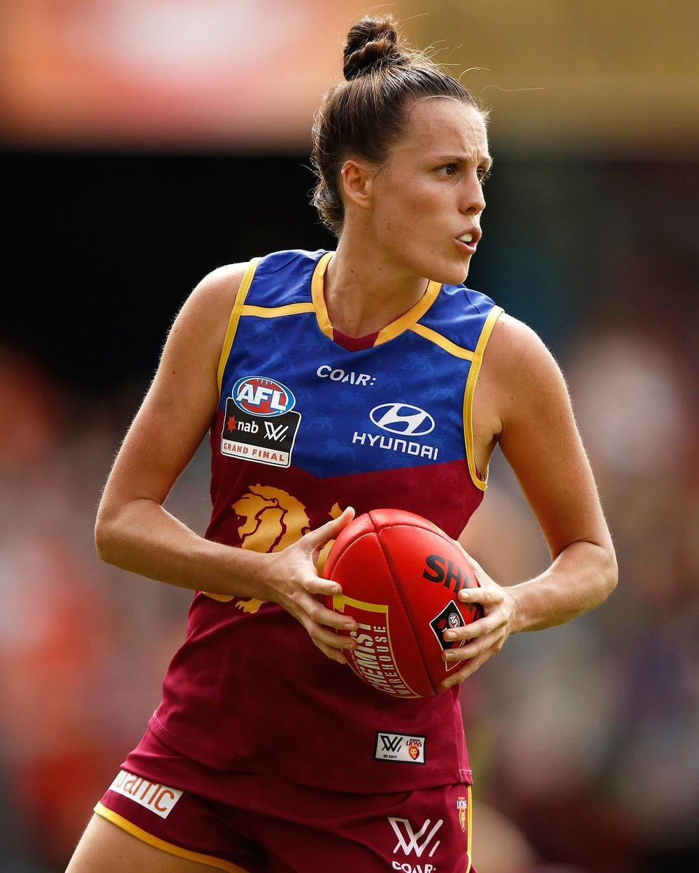 Emma Zielke holds the ball for the Brisbane Lions, mid-game, looking for a passing or kicking option
