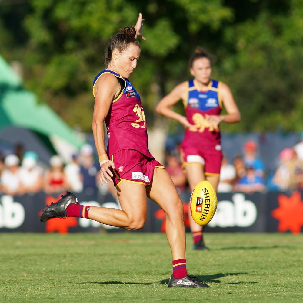 Emma Zielke playing for the Brisbane Lions, mid-kick during a game