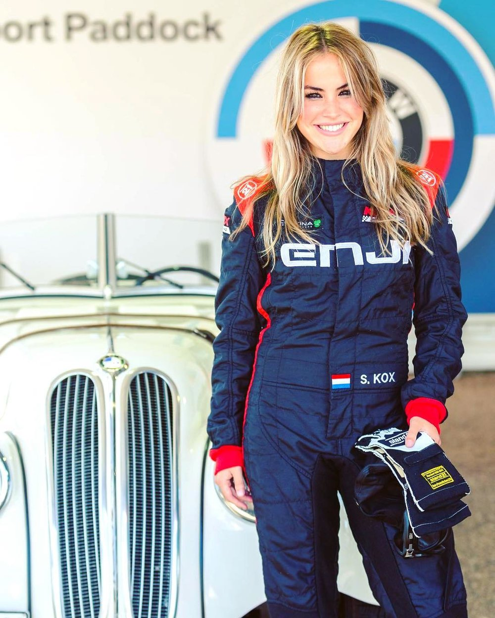 Stephane Kox poses in front of a vintage car in full modern racing gear, holding her gloves in her left hand.