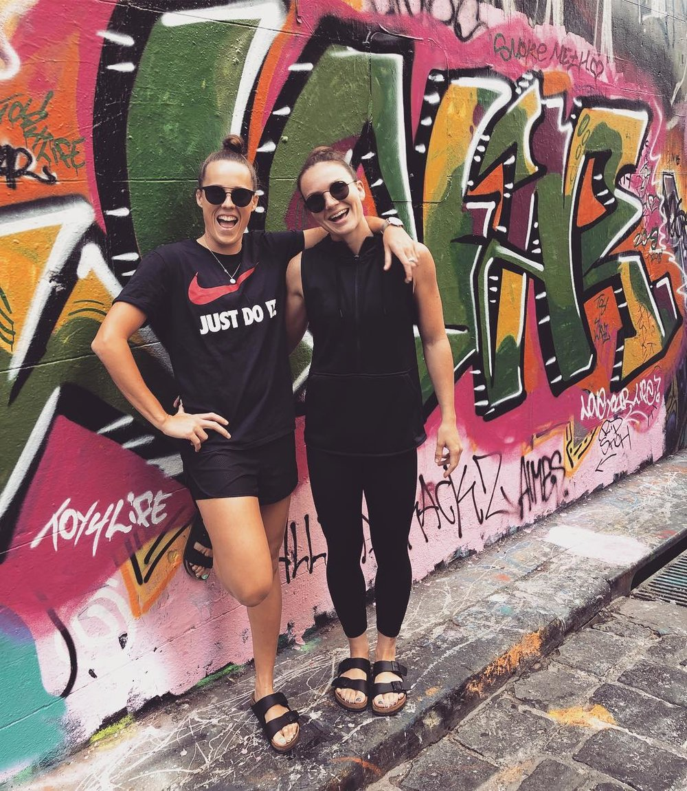 Emma Zielke has her arm around a friend, who are both posing on the street in front of some graffiti, wearing relaxed, black clothing