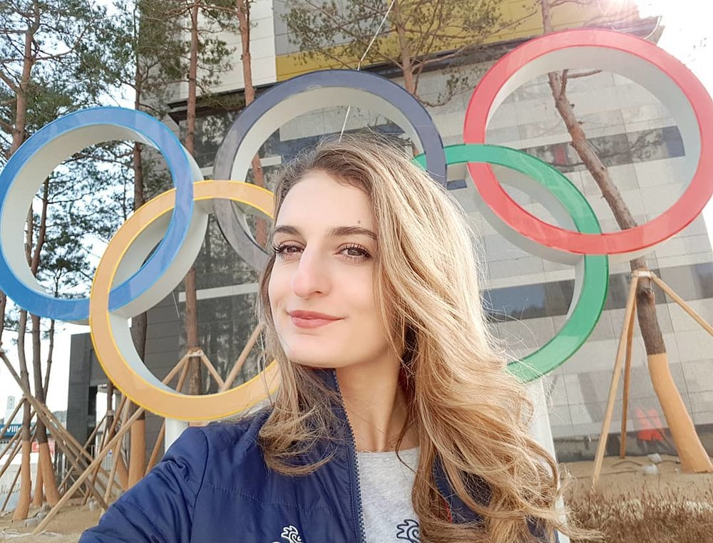 Gabriella Papadakis poses in front of the Olympic rings at the 2018 Winter Olympics