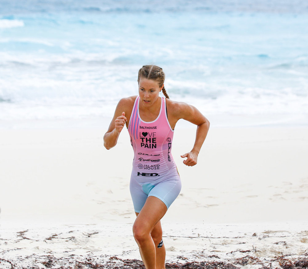 Ellie Salthouse at the end of the first stage of a triathlong, having just come out of the ocean , running across a beach