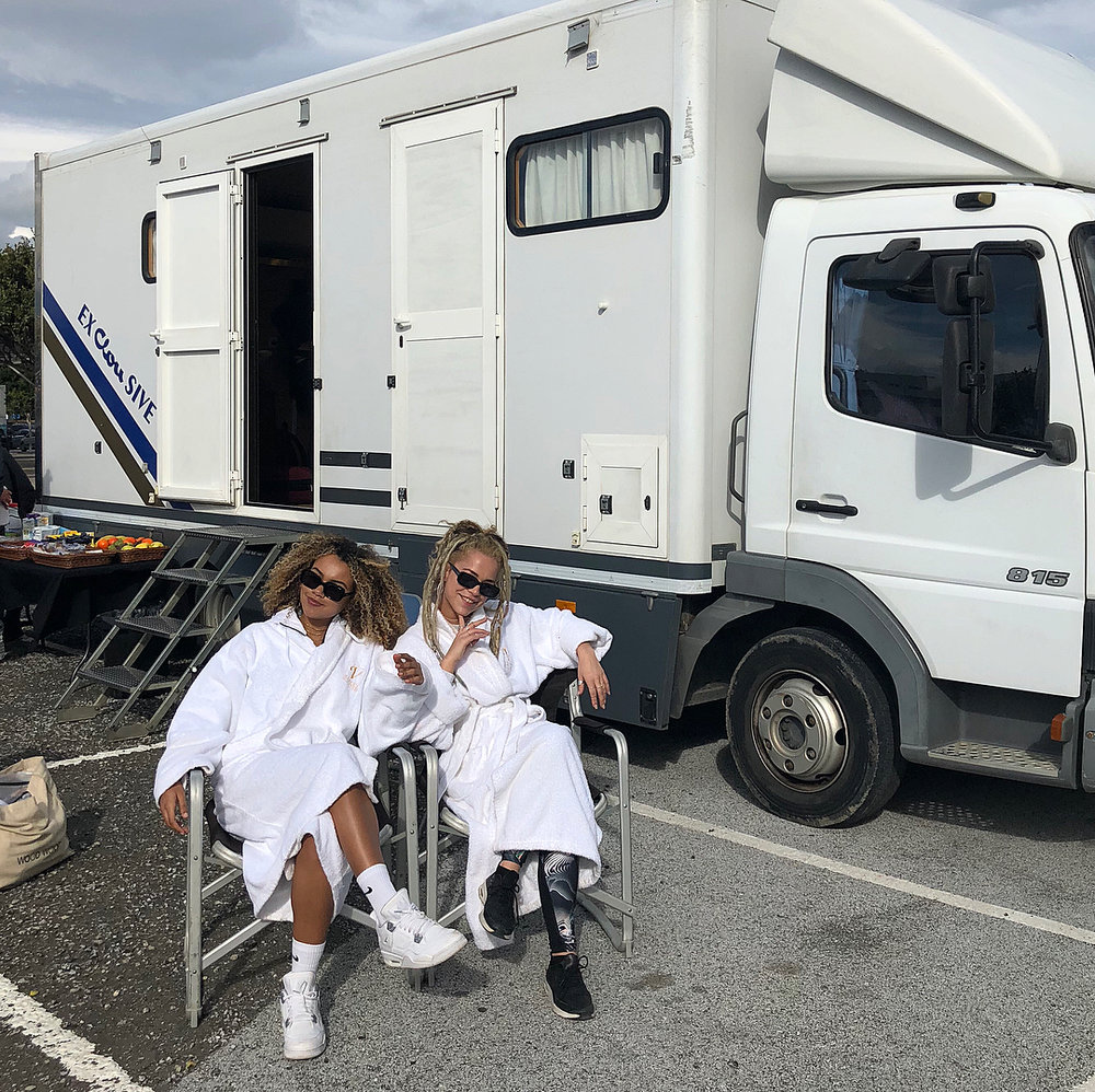 Ocean Lewis and a friend sit outside a Winnebago, on two pop-up chairs, wearing dressing gowns, in a car park