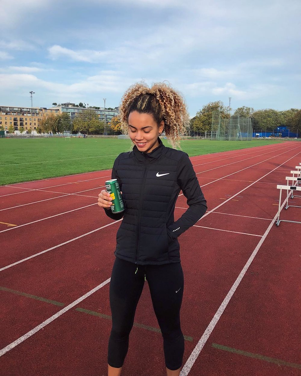 Ocean Lewis stood on a track in full Nike gear, drinking an energy drink and similing, looking at her feet