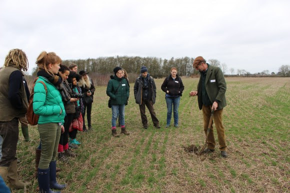 The collective standing on #OurField, with John showing off some of the no-till soil!