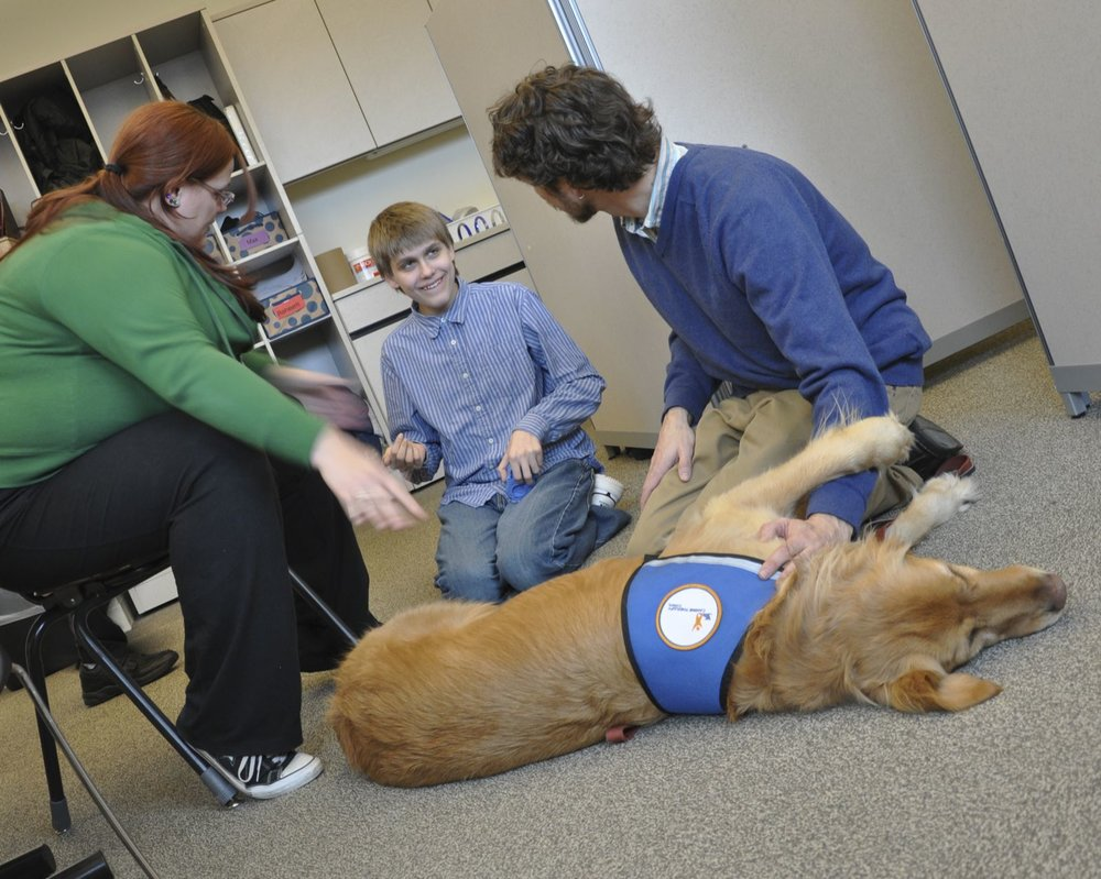 An Easter Seals student pets therapy dog Buddy (photo courtesy of Joy Schmoll)