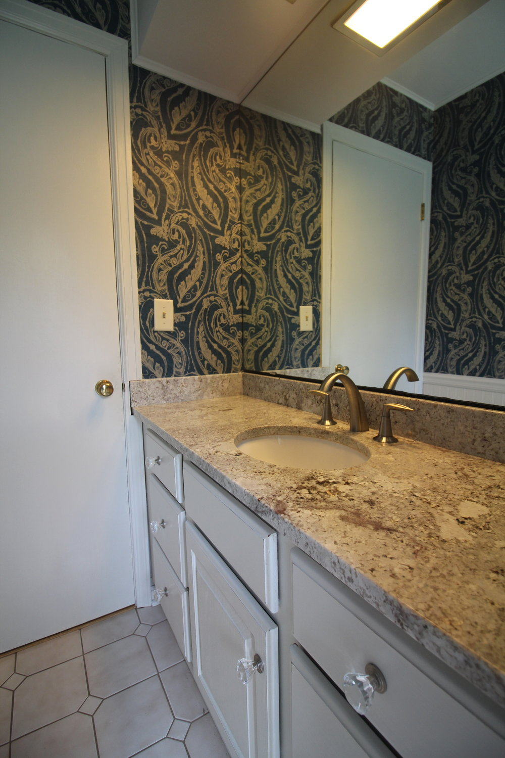 Powder Room Transformation    A renewed look for this powder room transformation. Painted cabinets, new counter tops and plumbing fixtures with a jazzy wallpaper refreshed this bathroom.