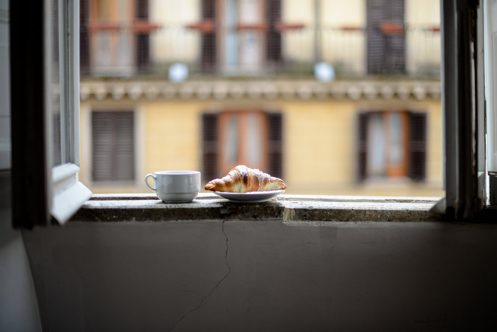 coffee and croissant on a windowsill in rome