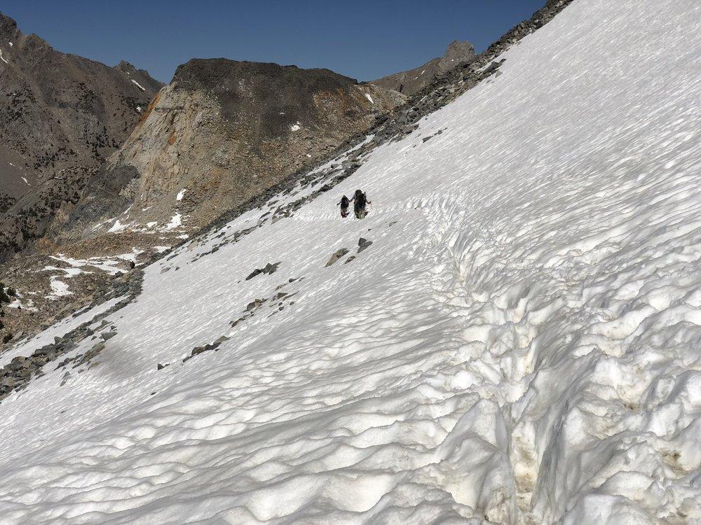 Trekking across snow at Glen Pass