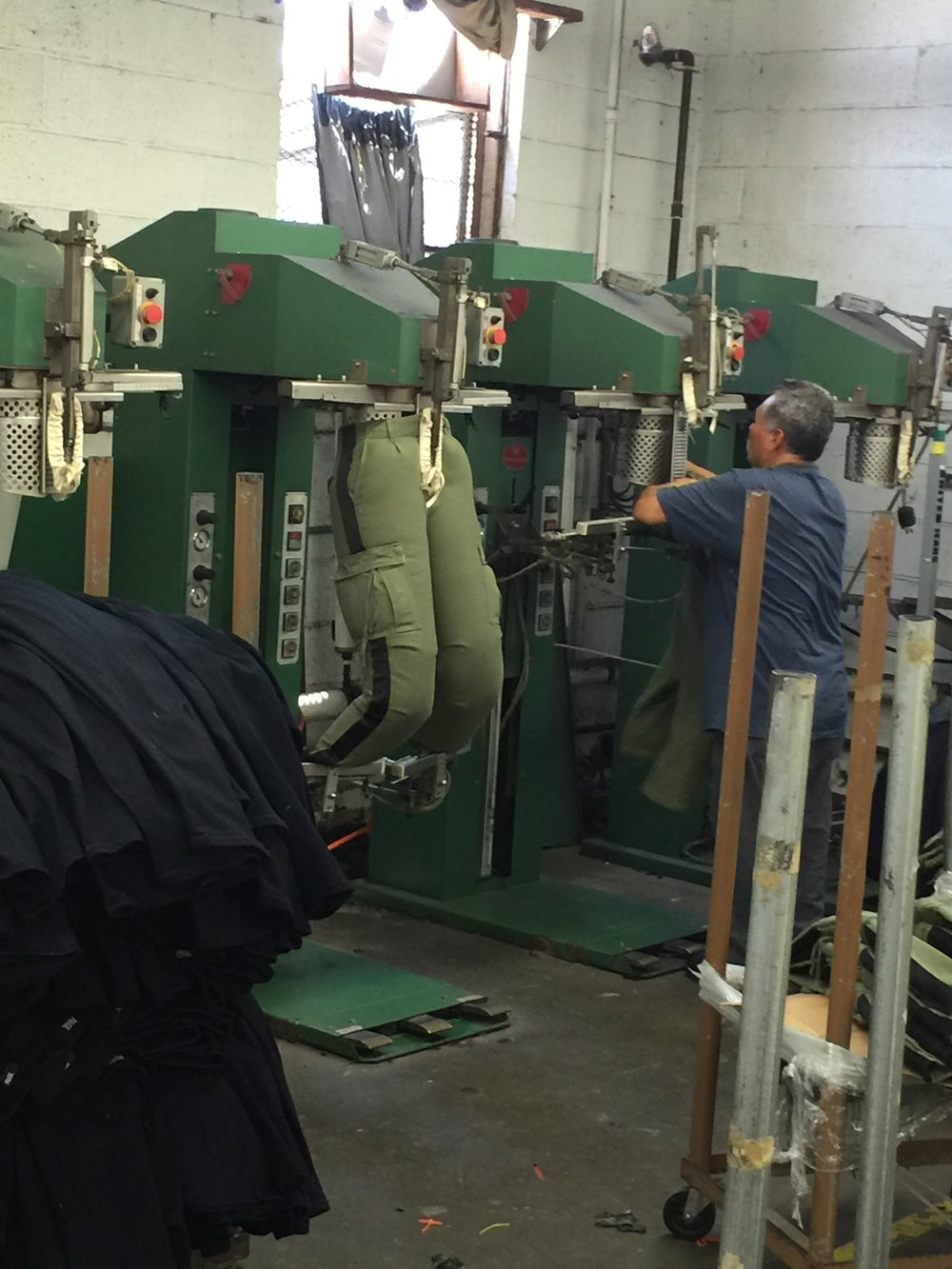 This is an image of what happens towards the end of the process, where they put the pants on the machine for a soft press before they fold and finish the pants.  There are many different ways to wash, but typically, the process is:  1.       Dry process - Handsand  2.       Spray potassium for fading and tinting  3.       Grinding adding holes, etc.  4.       Stone Wash – adding silicone softener if needed  5.       Dry  6.       Add resin which secures the color  7.       Put it through the oven to bake the resin  8.       Finish  These steps can go in various orders depending on what wash you'd like to achieve