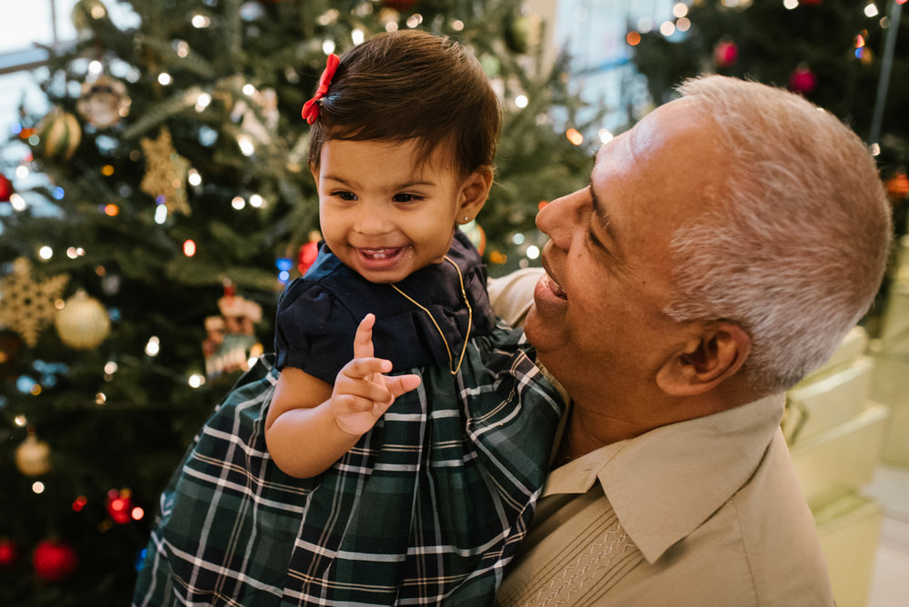 baby in holiday dress laughing with grandpa