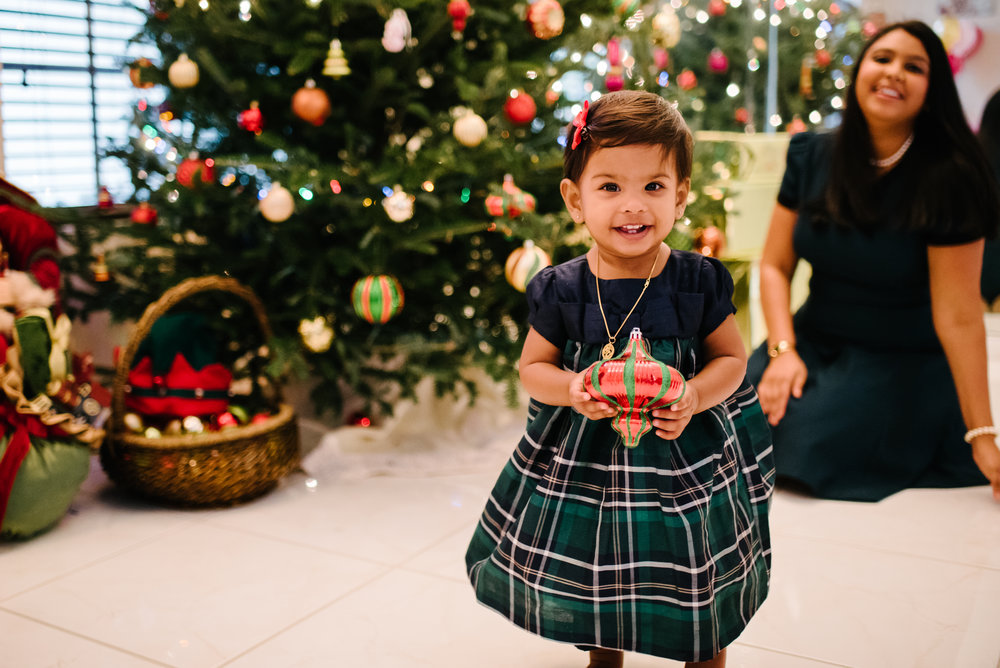baby with ornament in holiday dress with tree and smiling mom