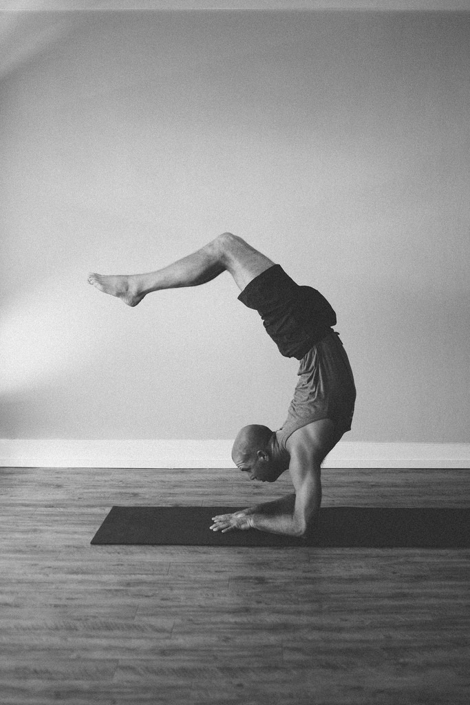 man in yoga pose in studio black and white