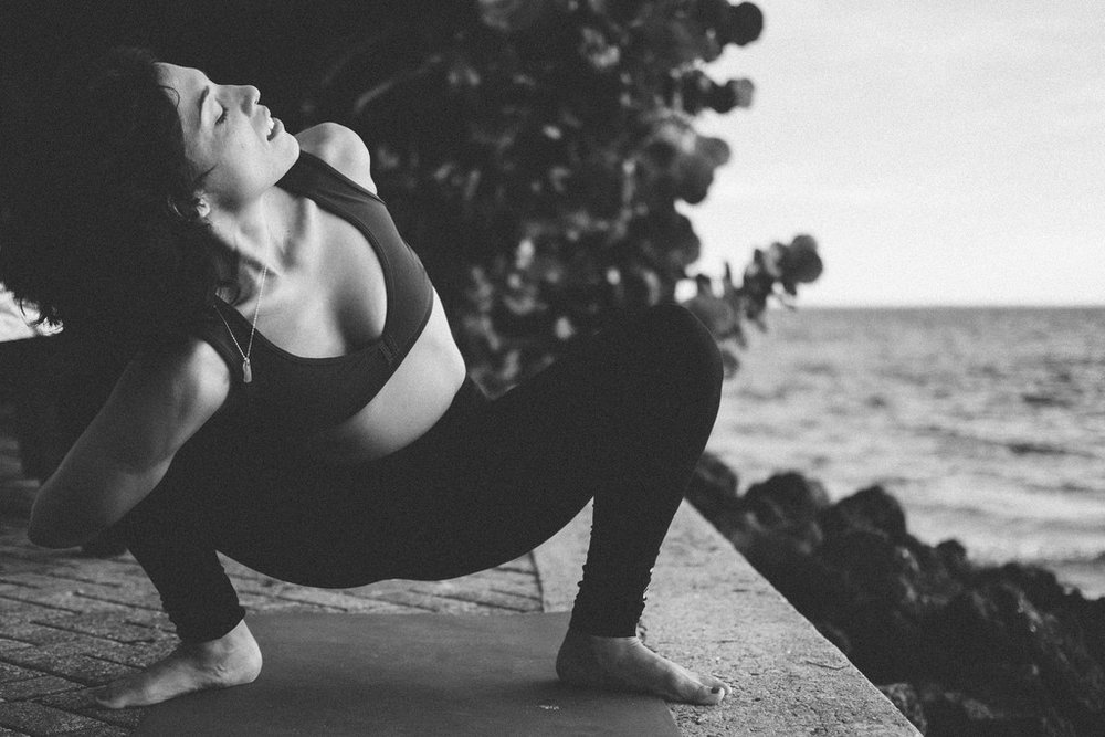 yogi woman in yoga pose by the water black and white