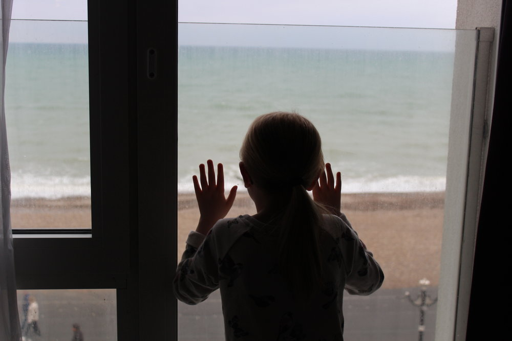sea front view worthing hotel, child gazing out of window