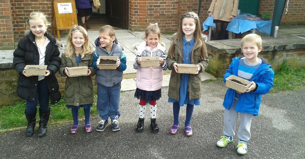 Young residents display the boxes they sowed dried peas in at one of the pop-up pea shoot events I organised.