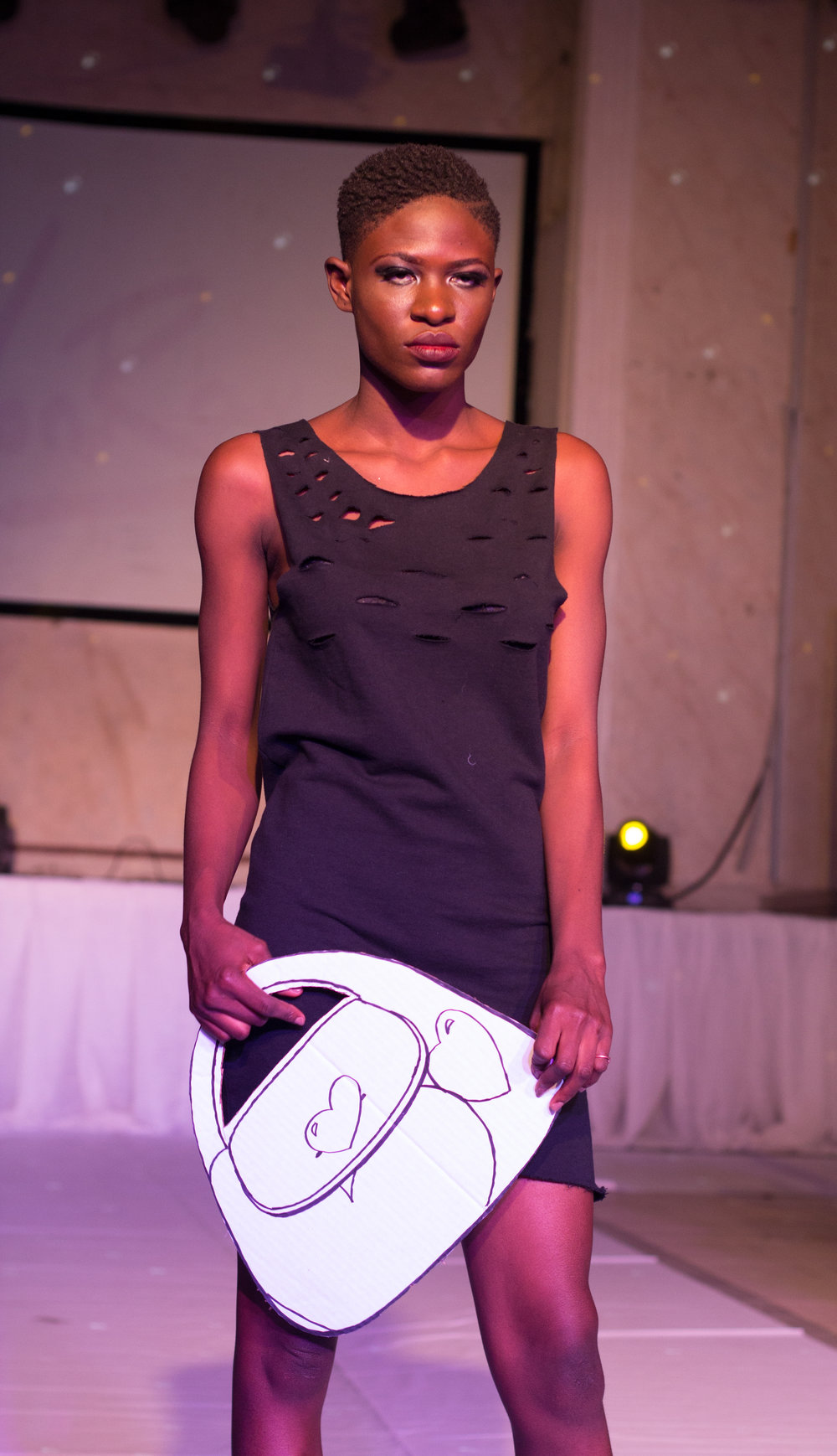 Nigerian Model @ The Eleventh Fashion Show wearing VonRay Designs Distressed Tee Dress and Paper-doll bag Illustrated by Dennis Robinson II of D2Artz & VonRay Designs; PHOTOGRAPHER- Ebiye Wilson Jeke of Wilson Photography (@wilsonjekephotography)