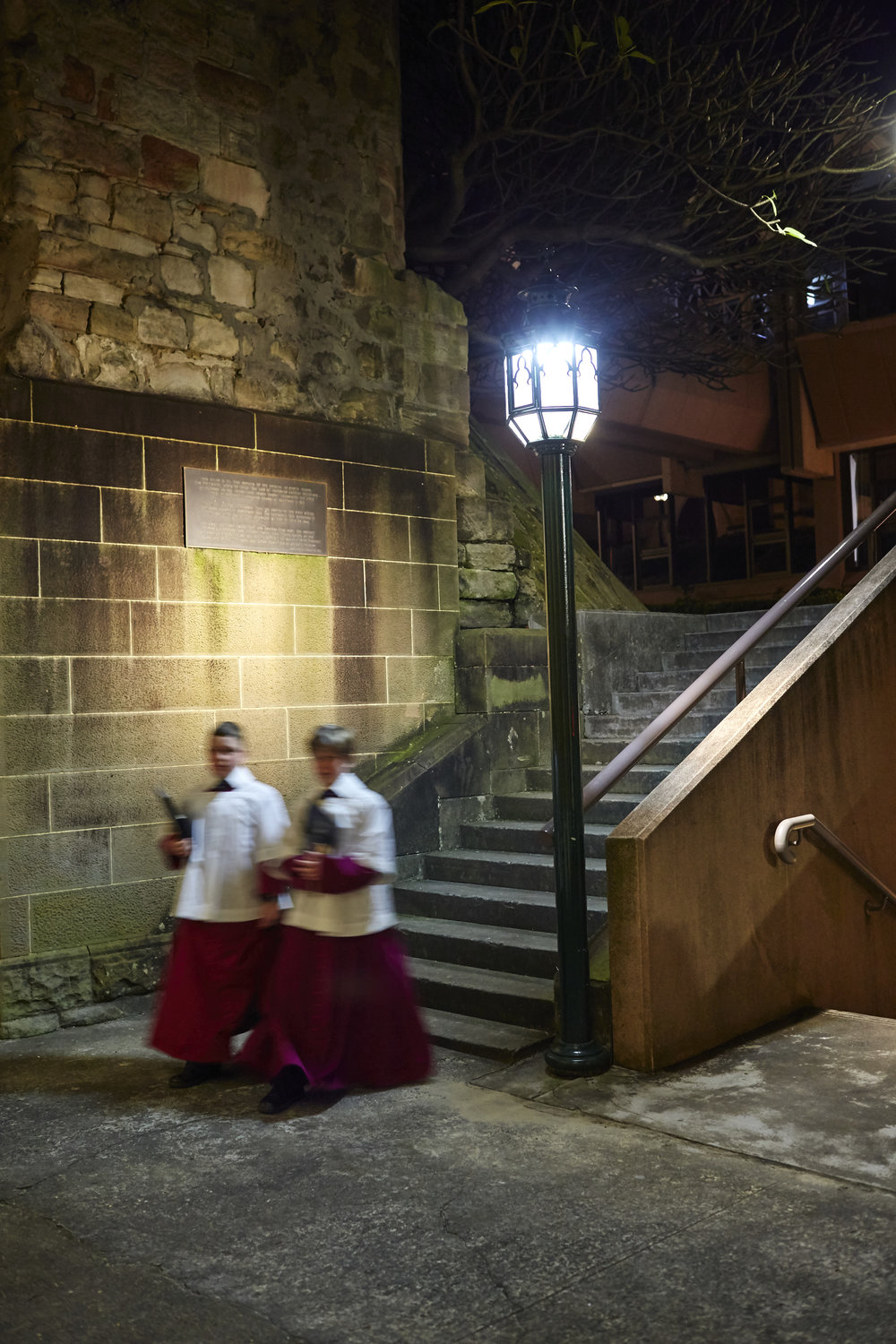 Two Choristers of Saint Mary's Cathedral Choir return walk past a lamp-post at night.