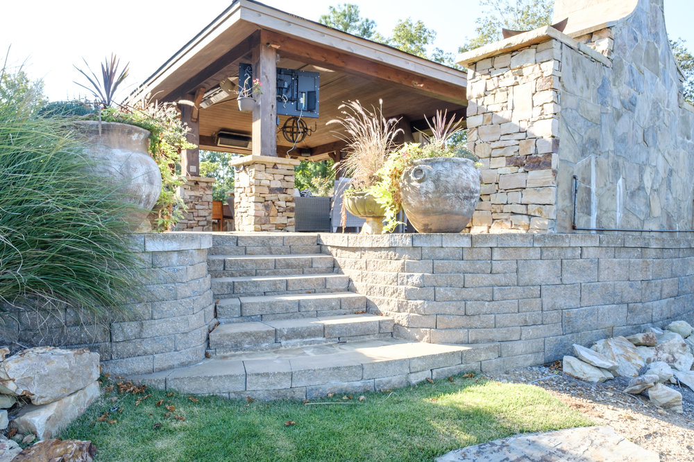 Stone stairs leading to outdoor kitchen and fireplace