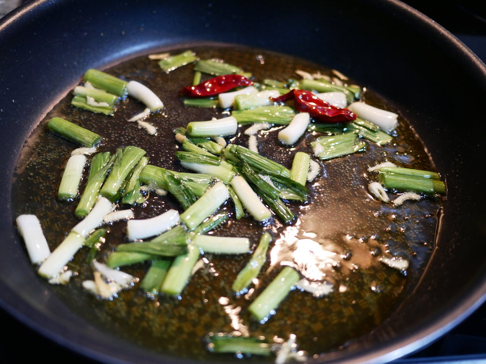 Frying green garlic and hot peppers