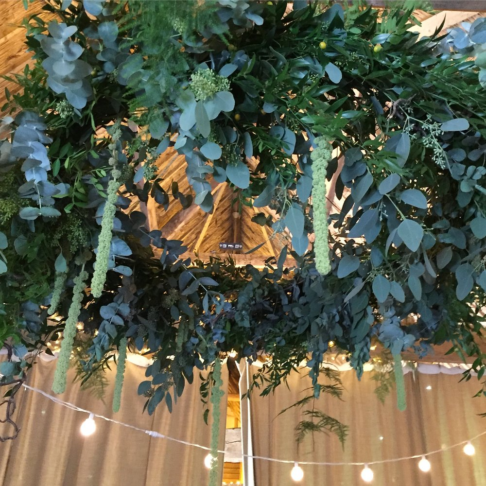 Hanging chandelier full of eucalyptus, ferns and amaranthus