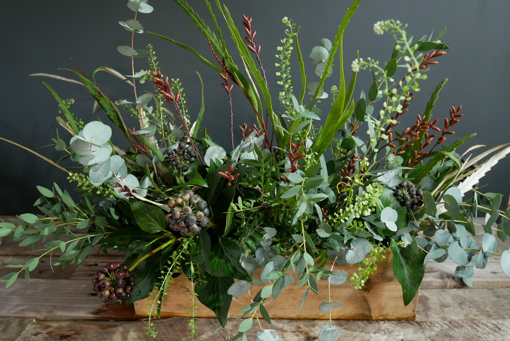 Rustic wooden crate full of foliage and berries