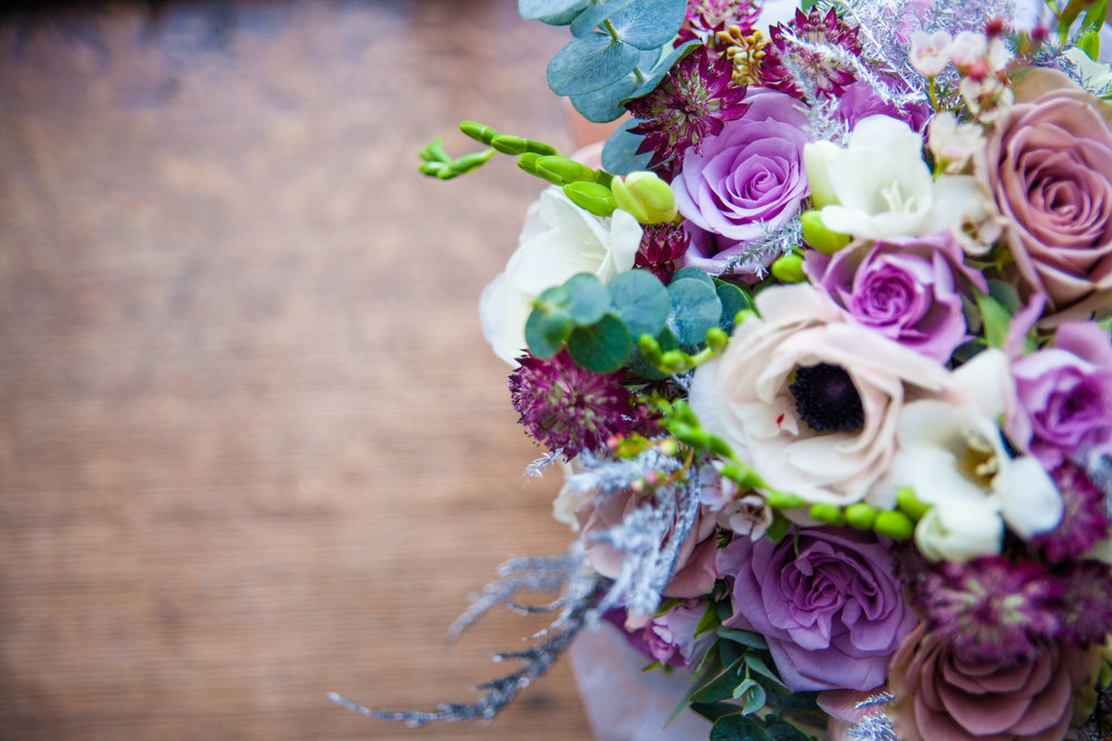 Wintry lilac bouquet full of roses, astrantia, anemones and roses