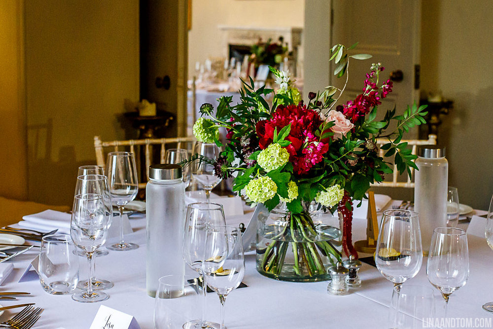 Wedding table set up at Aynhoe Park with large contemporary vase full of viburnum, peonies, snapdragons and astrantia by The Flower Story