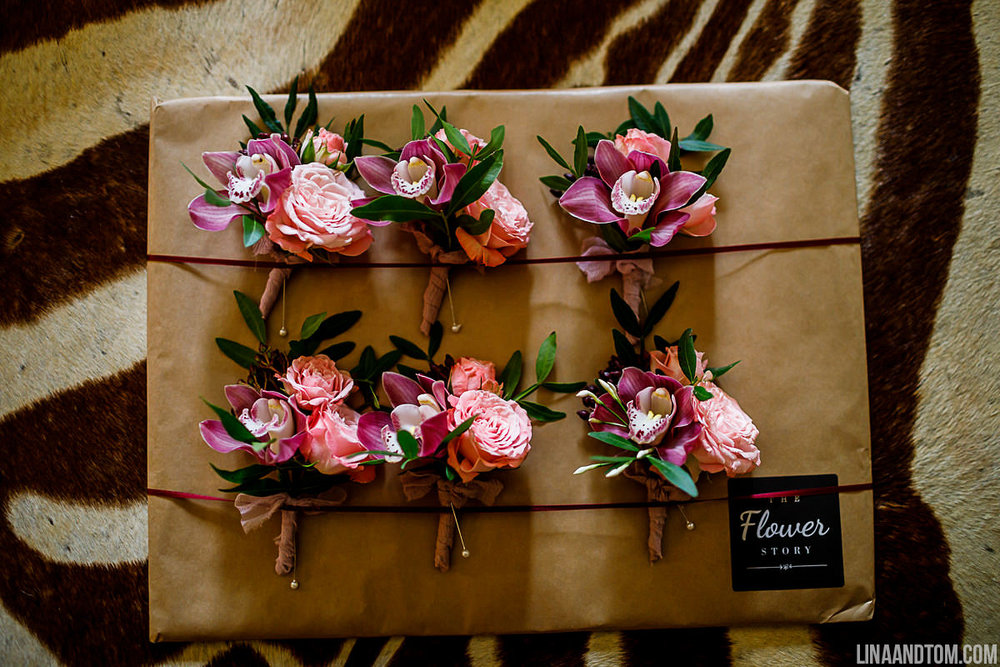 Spray rose, jasmine and orchid buttonholes finished with raw silk ribbon for wedding at Aynhoe Park